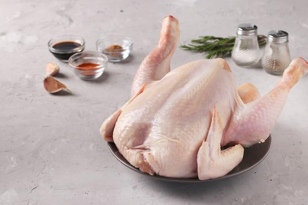 Pollo crudo e spezie: paprica, pepe, salsa di soia, aglio e rosmarino su uno sfondo di cemento grigio, primo piano, spazio per il testo