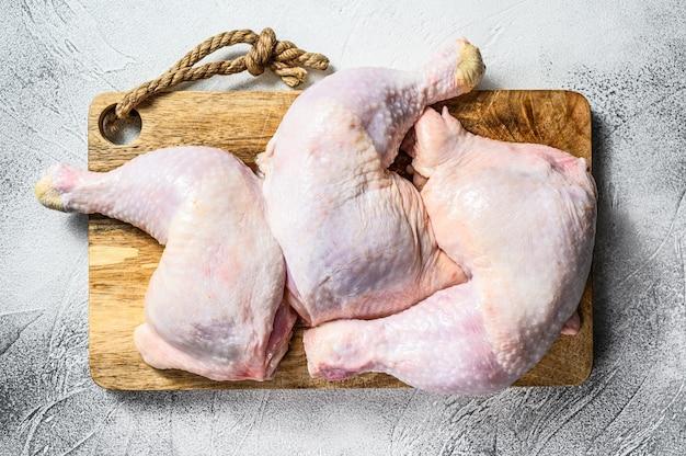 Cosce di pollo crude su un tagliere