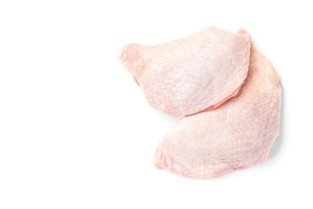 Cosce di pollo crude isolate su superficie bianca.