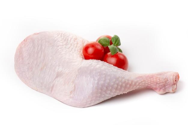 Cosce di pollo crude con pelle decorate con pomodori e basilico su sfondo bianco.