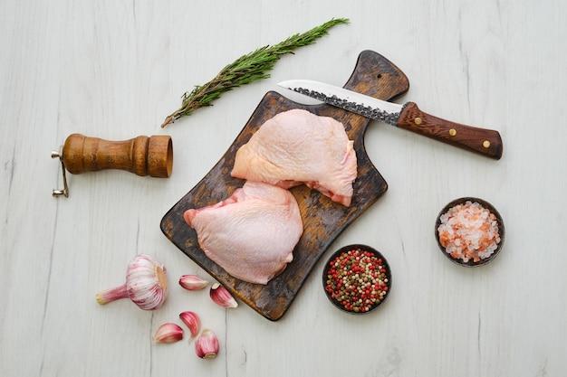 Cosce di pollo crude su tagliere di legno pronte per la cottura