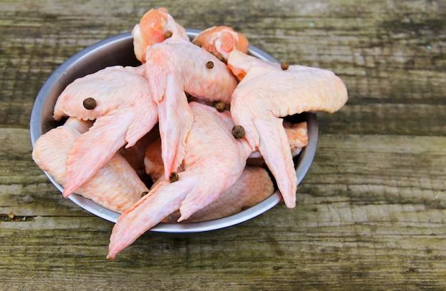 Ali di pollo crude in ciotola sulla tavola di legno rustica