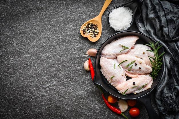Ali di pollo crude, erbe aromatiche e spezie con aglio pepe peperoncino pomodoro per cucinare, pollo rosmarino