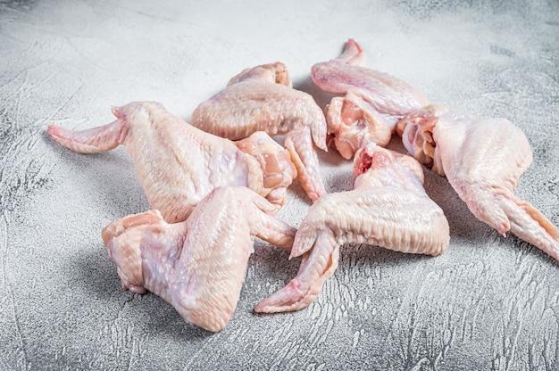 Ali di pollo crude su un tavolo da cucina.