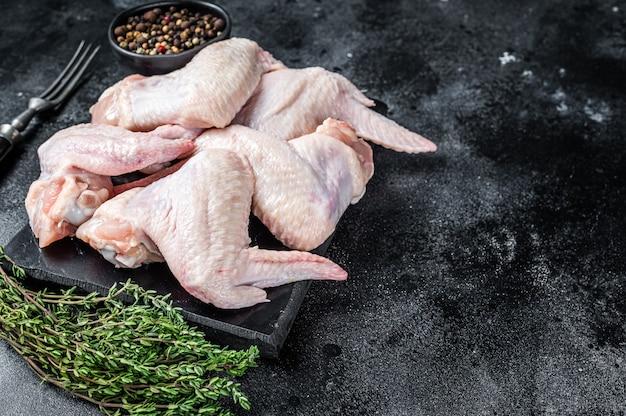 Ali di pollo crude carne di pollame su una tavola di marmo. sfondo nero. vista dall'alto. copia spazio.