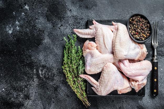 Ali di pollo crude carne di pollame su una tavola di marmo.