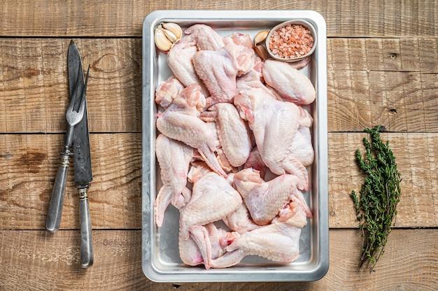 Ali di pollo crude carne di pollame pronta per la cottura con erbe aromatiche. fondo in legno. vista dall'alto.
