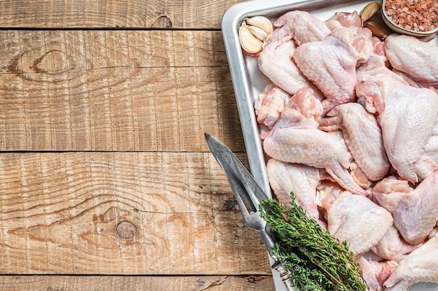 Ali di pollo crude carne di pollame pronta per la cottura con le erbe.