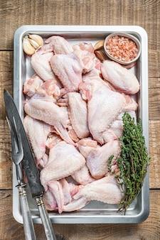 Alette di pollo crude carne di pollame pronta per la cottura con erbe