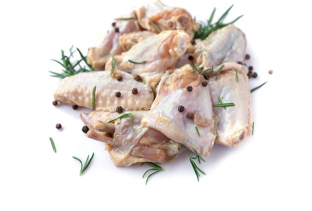 Ali di pollo crude con aglio, pepe e rosmarino isolate su fondo bianco
