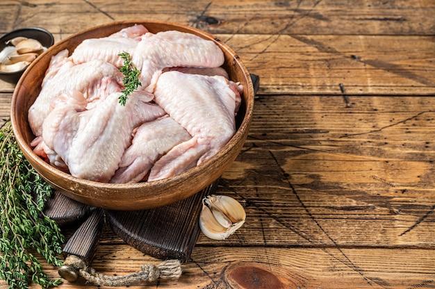 Ali di pollo crude in un piatto di legno con timo e aglio. fondo in legno. vista dall'alto. copia spazio.
