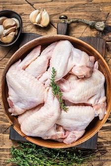 Ali di pollo crude in un piatto di legno con timo e aglio.