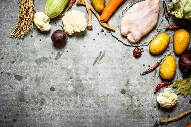 Pollo crudo con gli ingredienti per il tavolo in pietra di soupon.