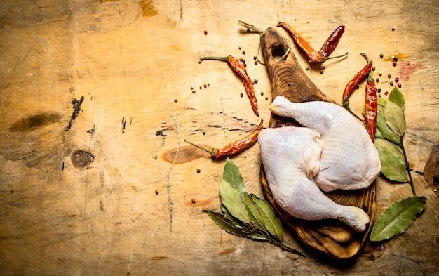 Pollo crudo con pepe in grani e foglie di alloro a bordo sulla tavola di legno.