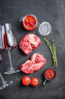 Tagli crudi della bistecca del rotolo dell'occhio del mandrino, con il vetro del vino rosso, rosmarino, olio piccante del peperoncino rosso sulla vista superiore del fondo strutturato nero.