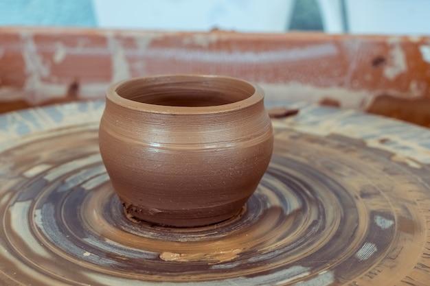 Argilla grezza, tazza finita si trova su un tornio da vasaio. ceramica dall'argilla alla brocca finita