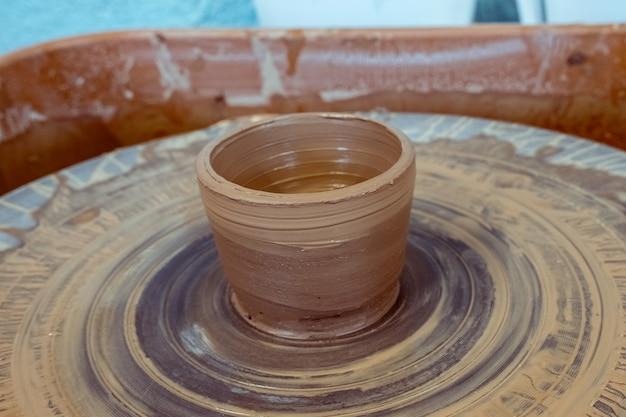 La tazza finita in argilla grezza si trova su un tornio da vasaio ceramica dall'argilla alla brocca finita