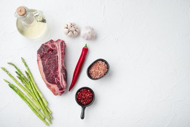 Bistecca cruda con set di ingredienti, su pietra bianca