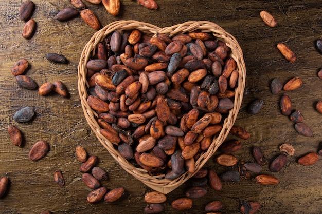 Fave di cacao crude in cestino a forma di cuore con vista dall'alto rustica.