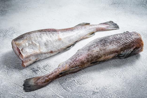 Pesce intero di merluzzo crudo sul tavolo della cucina. vista dall'alto.