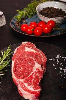 Carne di manzo colorata cruda su una tavola di ardesia pronta per grigliare. immagine verticale