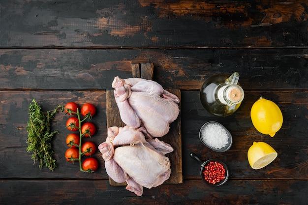 Polli crudi coquelet carne con ingredienti, su un vecchio tavolo di legno, vista dall'alto