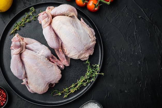 Polli crudi del coquelet con gli ingredienti delle spezie delle erbe, sul nero