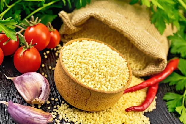 Cous cous crudo in una ciotola e un sacco di tela, aglio, pomodori, peperoncino ed erbe aromatiche sullo sfondo di una tavola di legno scuro