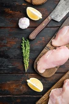 Filetto di pollo crudo con l'ingrediente, sul tavolo di legno scuro, vista dall'alto