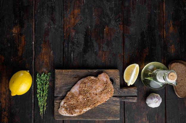 Filetto di pollo crudo con ingrediente, su tavola di legno, piatto