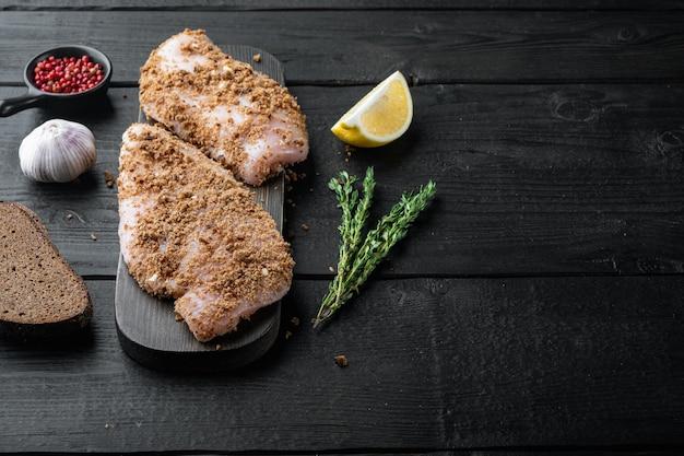 Filetto di pollo crudo con ingredienti, su un tavolo di legno nero con spazio per le copie