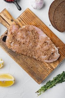 Filetto di pollo crudo con ingredienti su sfondo bianco, vista dall'alto