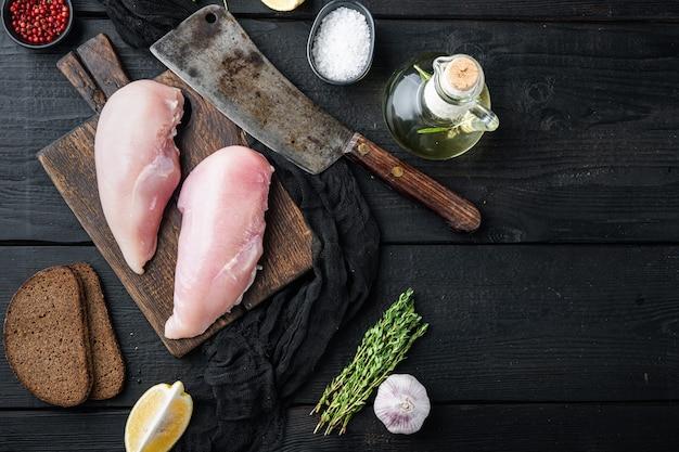 Filetto di pollo crumbet crudo con ingredienti con coltello da macellaio sulla tavola di legno nera, vista dall'alto