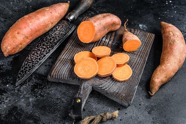 Batata tagliata cruda patata dolce sul tagliere di legno.
