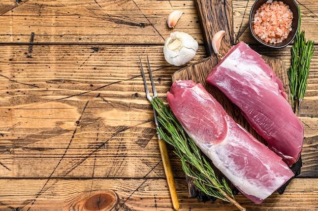Carne di filetto di maiale tagliata cruda. fondo in legno. vista dall'alto. copia spazio.
