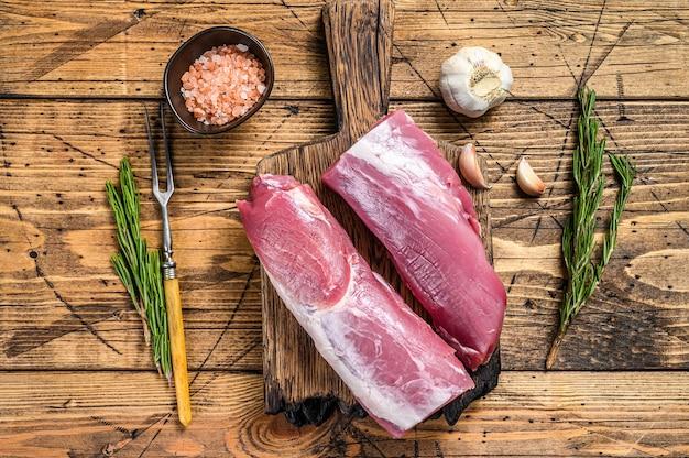 Carne di filetto di maiale tagliata cruda. fondo in legno. vista dall'alto.