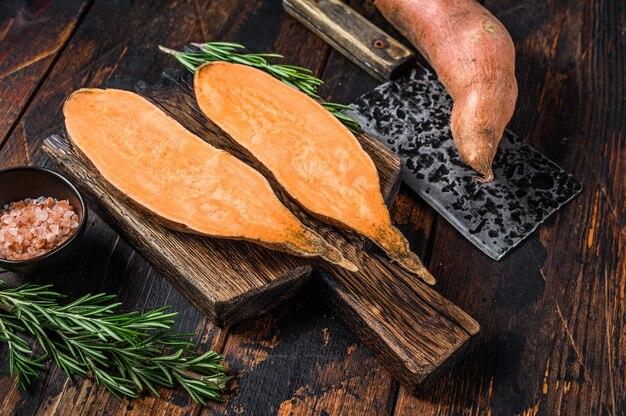 Patata dolce tagliata cruda sul tagliere di legno.