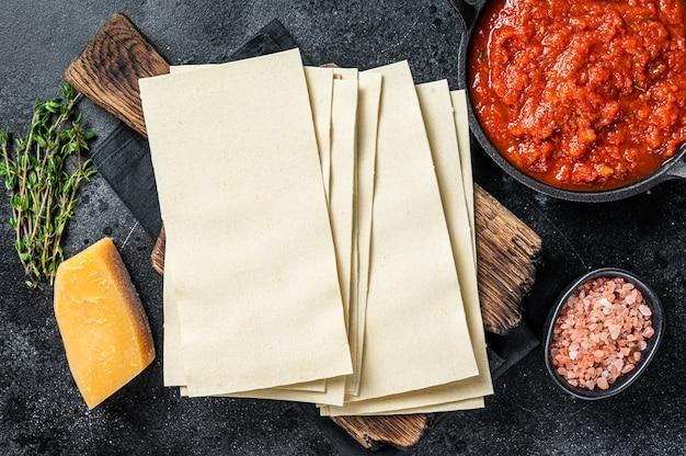 Materie diverse ingredienti per cucinare le lasagne italiane su un tavolo da cucina. sfondo nero. vista dall'alto.