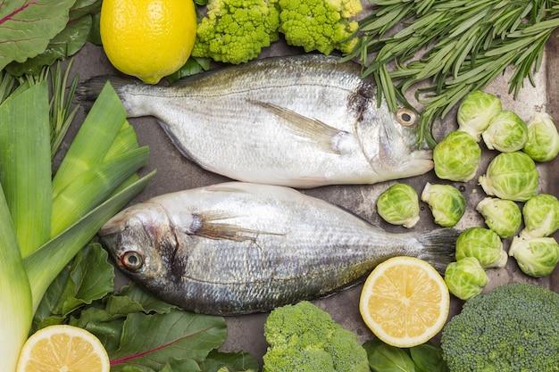 Pesce crudo dorado sul vassoio di metallo con verdure verdi e vegetazione
