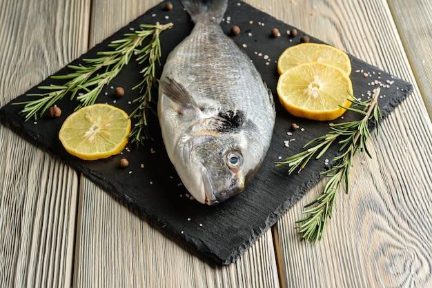 Pesce crudo di dorado con fette di limone e primo piano di rosmarino.