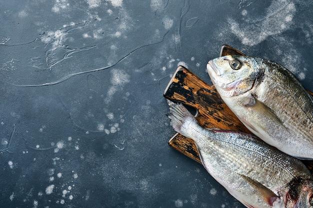 Pesce fresco crudo dorado o orata con ingredienti per fare limone, timo, aglio, pomodorini e sale su uno sfondo di ardesia nera, pietra o cemento. vista dall'alto con copia spazio.