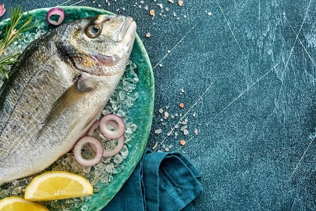 Pesce fresco crudo di dorado o orata con ingredienti per preparare limone, timo, aglio, pomodorini e sale su ghiaccio su uno sfondo di ardesia nera, pietra o cemento. vista dall'alto con copia spazio.