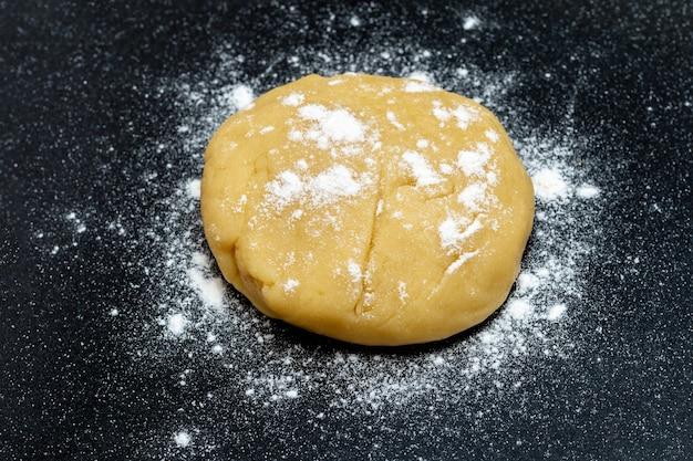 Pasta cruda per pane o pizza su uno sfondo nero, primo piano, vista dall'alto