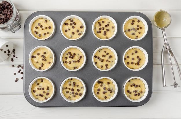 Pasta cruda per muffin con gocce di cioccolato in forma di cottura su un fondo di legno bianco.