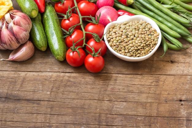 Lenticchie verdi asciutte crude in una ciotola e verdure su una fine di legno della tavola su con lo spazio della copia