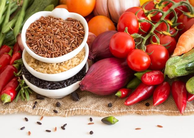 Riso organico rosso, nero e non lucidato asciutto crudo in ciotole con le verdure su un isolato della tela da imballaggio sulla fine di bianco su