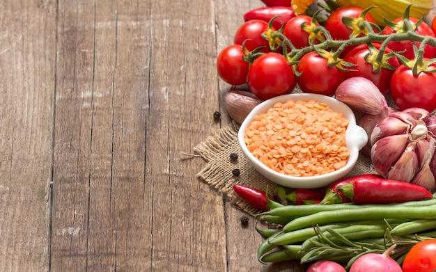 Lenticchie rosse asciutte crude in una ciotola e verdure su una fine di legno della tavola su con lo spazio della copia