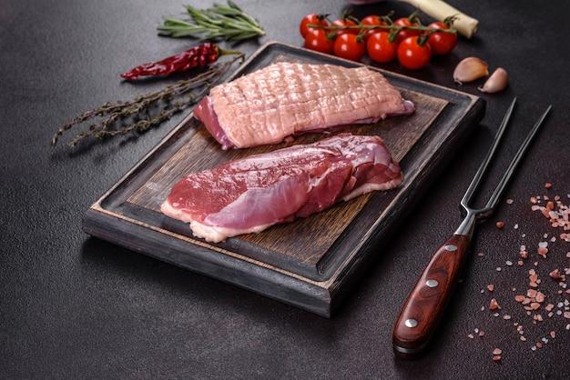 Petto d'anatra crudo con erbe e spezie su uno sfondo di cemento scuro. carne cruda preparata per la cottura