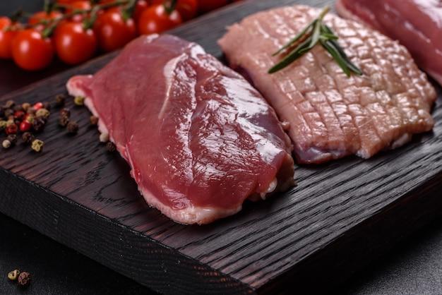 Petto d'anatra crudo con erbe e spezie su una superficie di cemento scuro. carne cruda preparata per la cottura