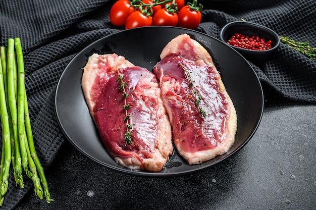 Petti d'anatra crudi su un piatto. carne di pollame biologica